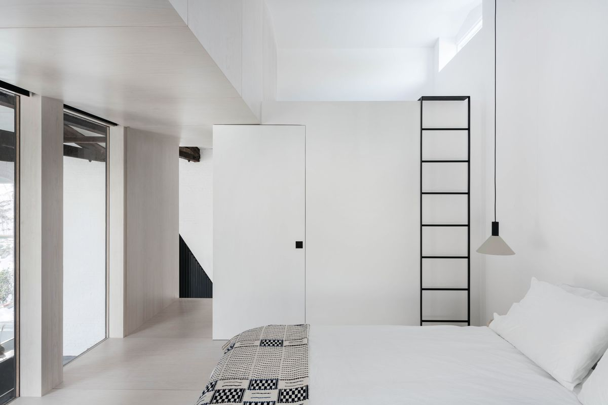 All-white bedroom with a black ladder and black-and-white patterned throw.