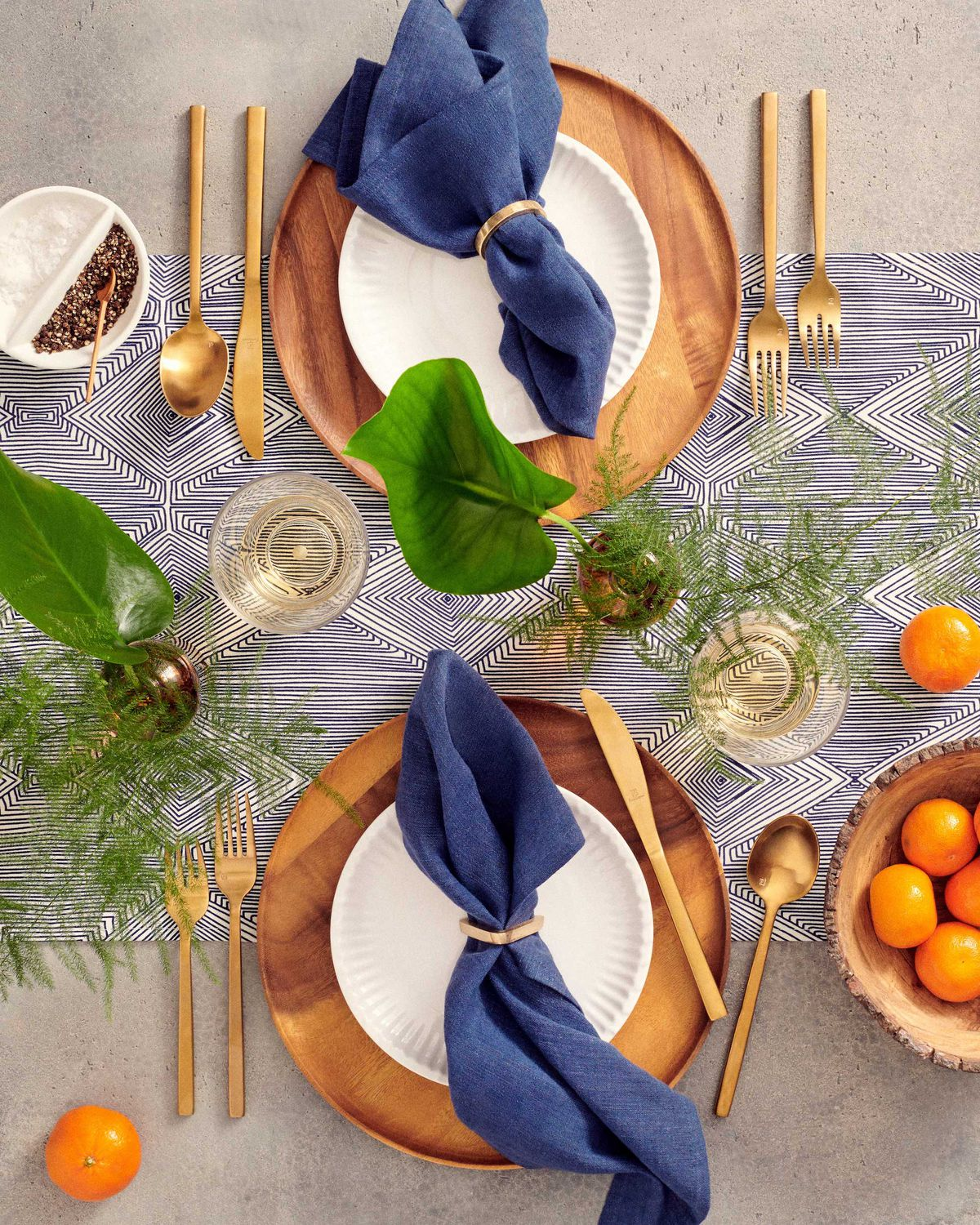 Place setting with wooden plate, gold flatware, and dark blue napkins.