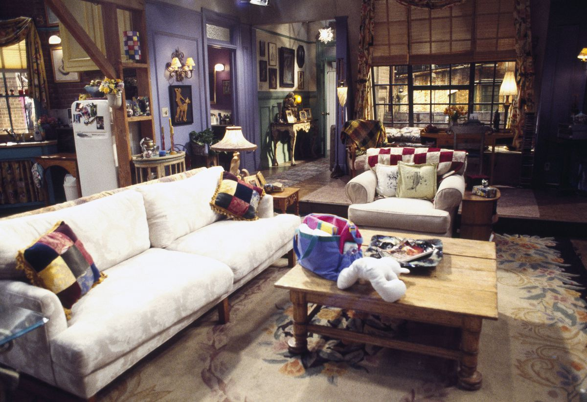 Monica's apartment in the TV show Friends. There is a couch, armchair, and coffee table. There is a patterned area rug. The living area is joined to a kitchen and a dining area.