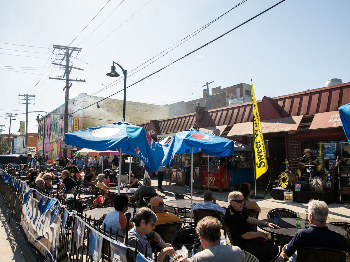 blue pepsi umbrellas and yellow flags surround people seated on a patio in front of Bert's Marketplace