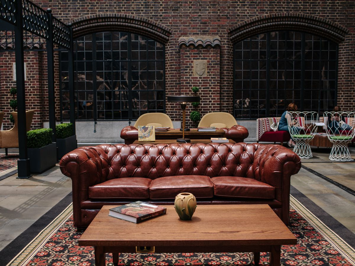A red leather couch on an oriental rug with a coffee table inside Kresge Court.