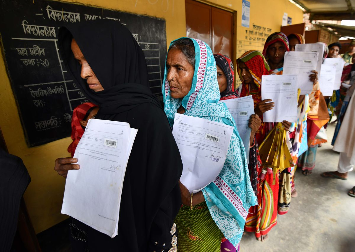 Indian women wrapped in scarves hold their documents as they stand in line to check their names on the National Register of Citizens.