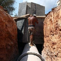 A worker stands on a concrete sewage pipe at a construction site in Athens, Thursday, Sept. 6, 2012. Greece's unemployment rate surged to 24.4 percent in June, according to official figures Thursday, as protests continued against a massive new austerity package, with police blocking their colleagues from starting work.