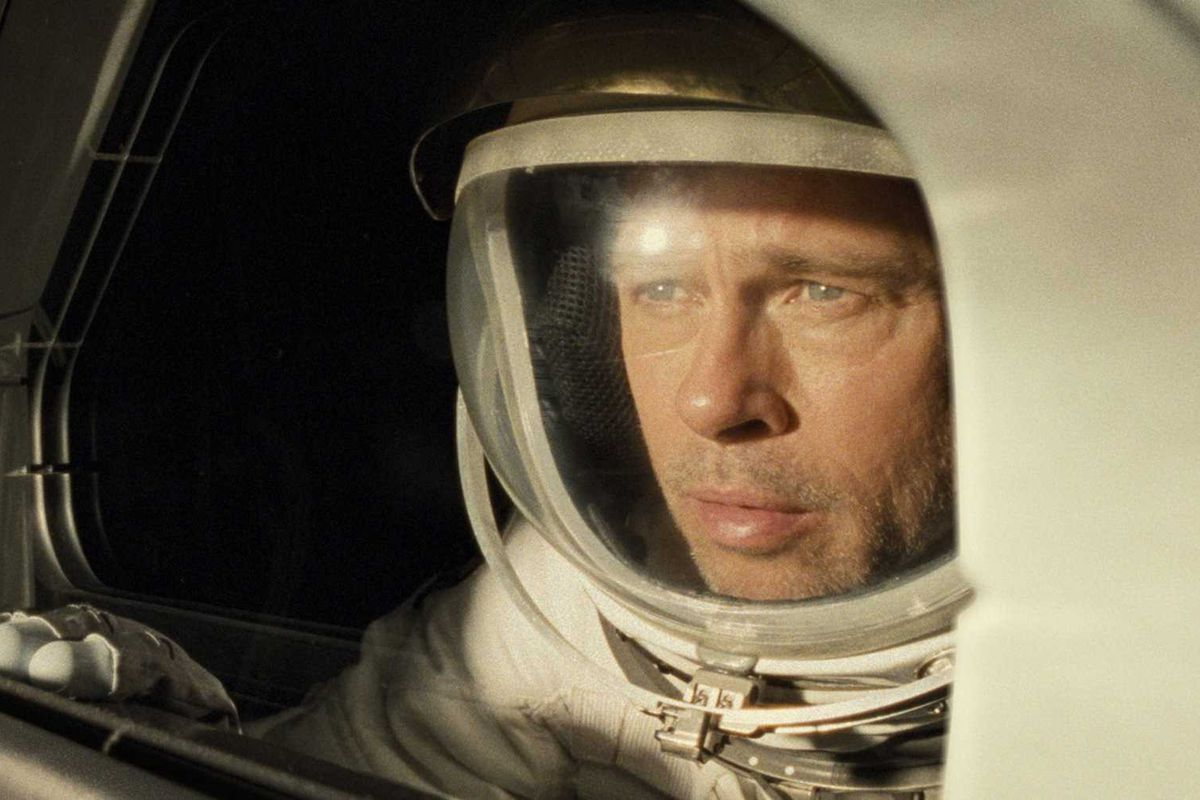 "Brad Pitt wearing a spacesuit and peering out of his spacecraft in the movie ""Ad Astra."""