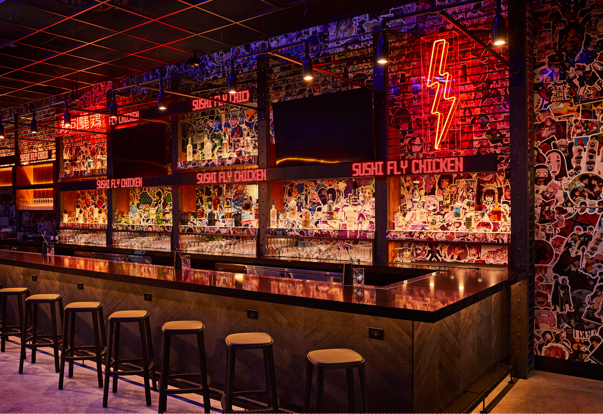 large bar top area with neon signs in background and murals on wall