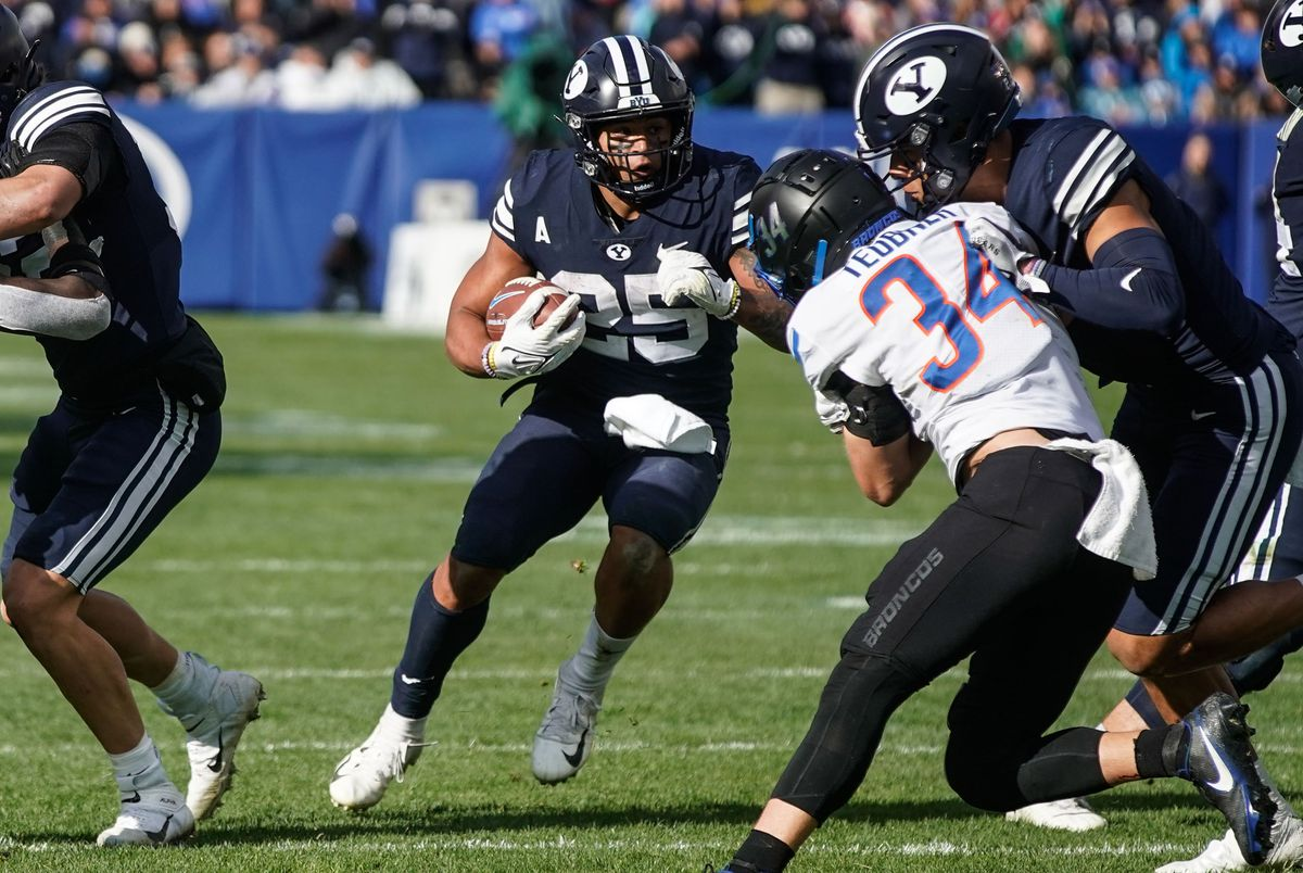 BYU running back Tyler Allgeier runs past Boise State defenders for a touchdown during game at LaVell Edwards Stadium in Provo on Saturday, Oct. 9, 2021.