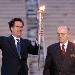 SLOC member Mitt Romney waves to the crowd after getting the torch from Hellenic Olympic Committee president Lambis Nikolaou  in Athens, Greece,  Dec. 3, 2001.
