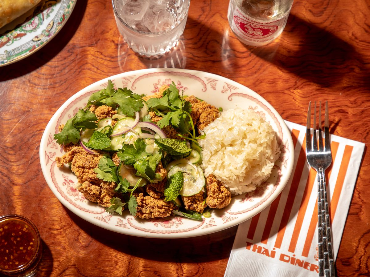 Nuggets of golden fried chicken sit underneath green herbs and next to a pile of white rice