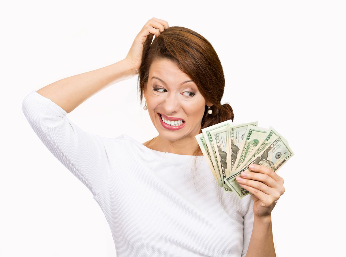 A woman confusedly holds up cash