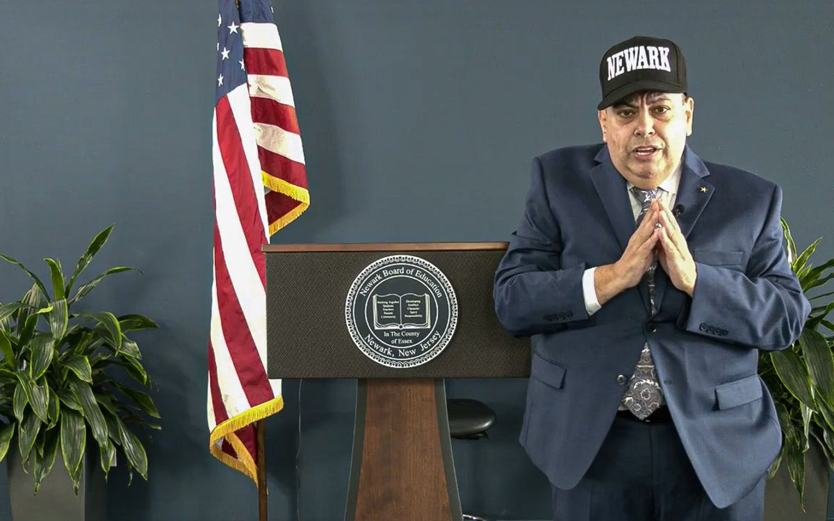 Newark Superintendent Roger León speaks at a podium, wearing a blue suit and Newark hat, during a virtual convocation.