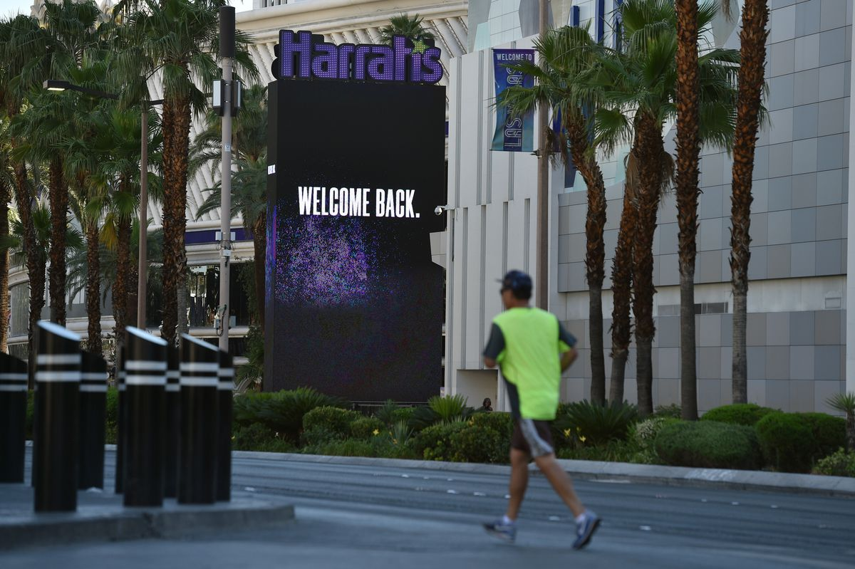 """Man in yellow shirt runs past large electronic sign on a building reading """"Harrah's, Welcome Back."""""""