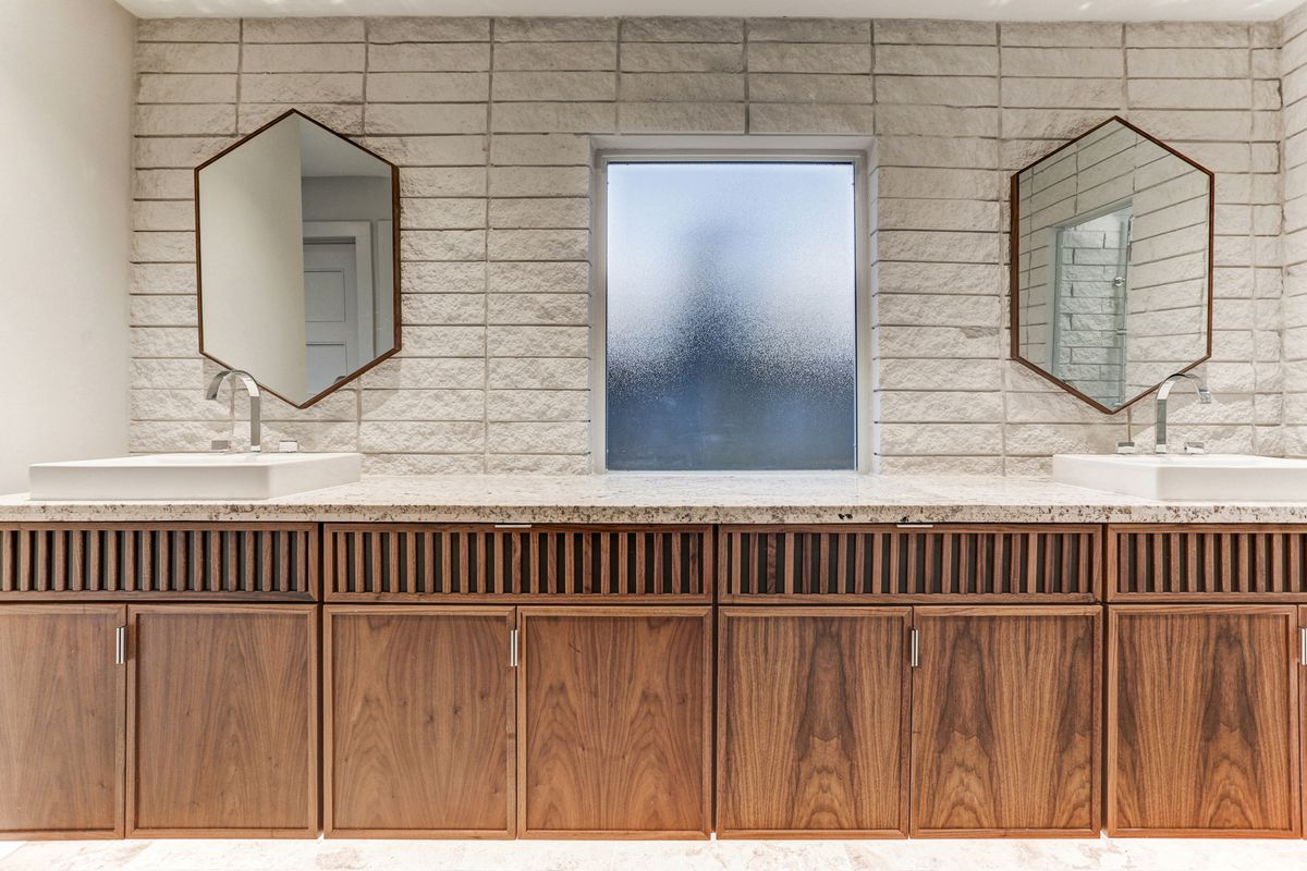 A master bath has two sinks, two mirrors, and a long set of cabinets.