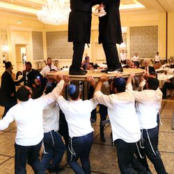 Rabbi Benny Zippel and his son-in-law, Rabbi Mendy Cohen, are lifted onto a table during a traditional Chabad Lubavitch Jewish wedding at the Grand America Hotel in Salt Lake City on Monday, Sept. 12, 2016.