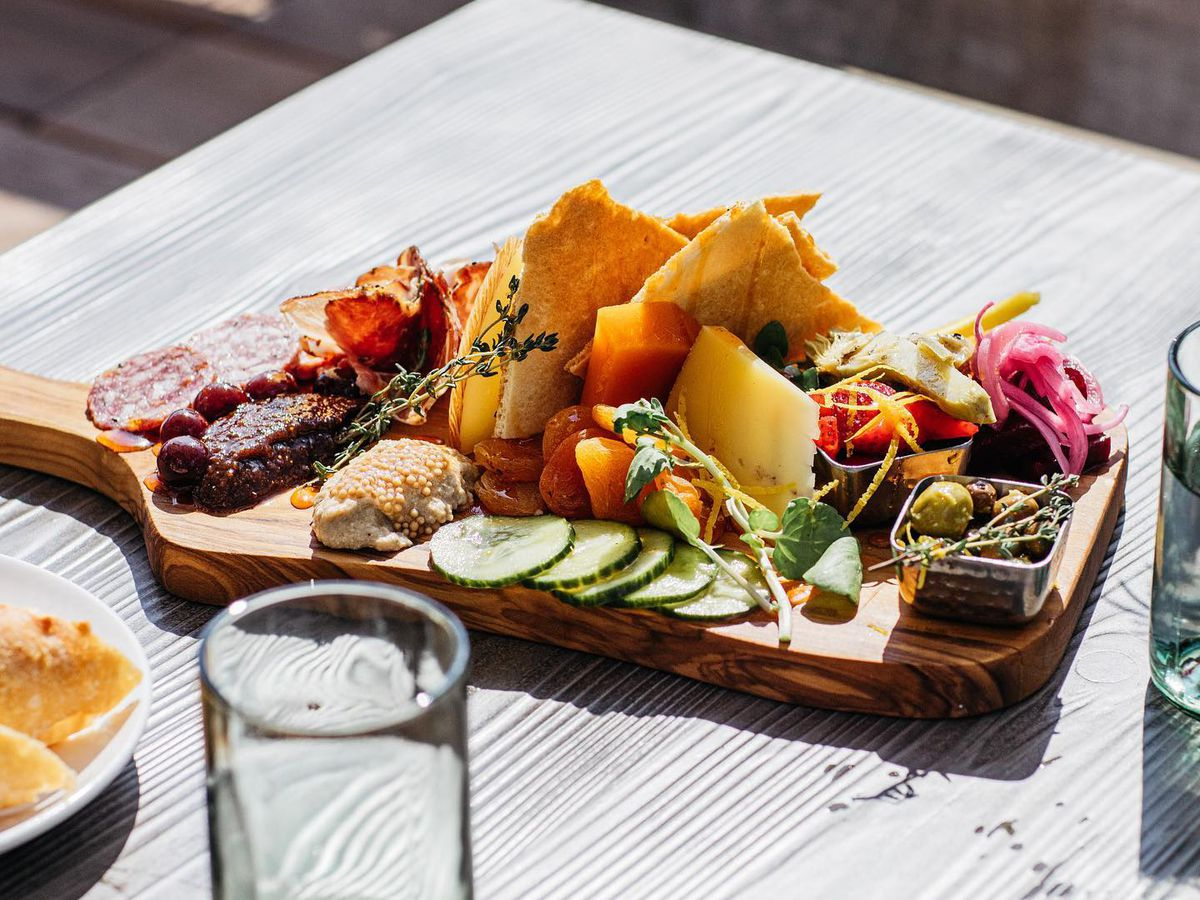 A charcuterie board is piled on a handled cutting board with salamis, cheeses, and homemade crackers, almost glowing in bright afternoon sun.