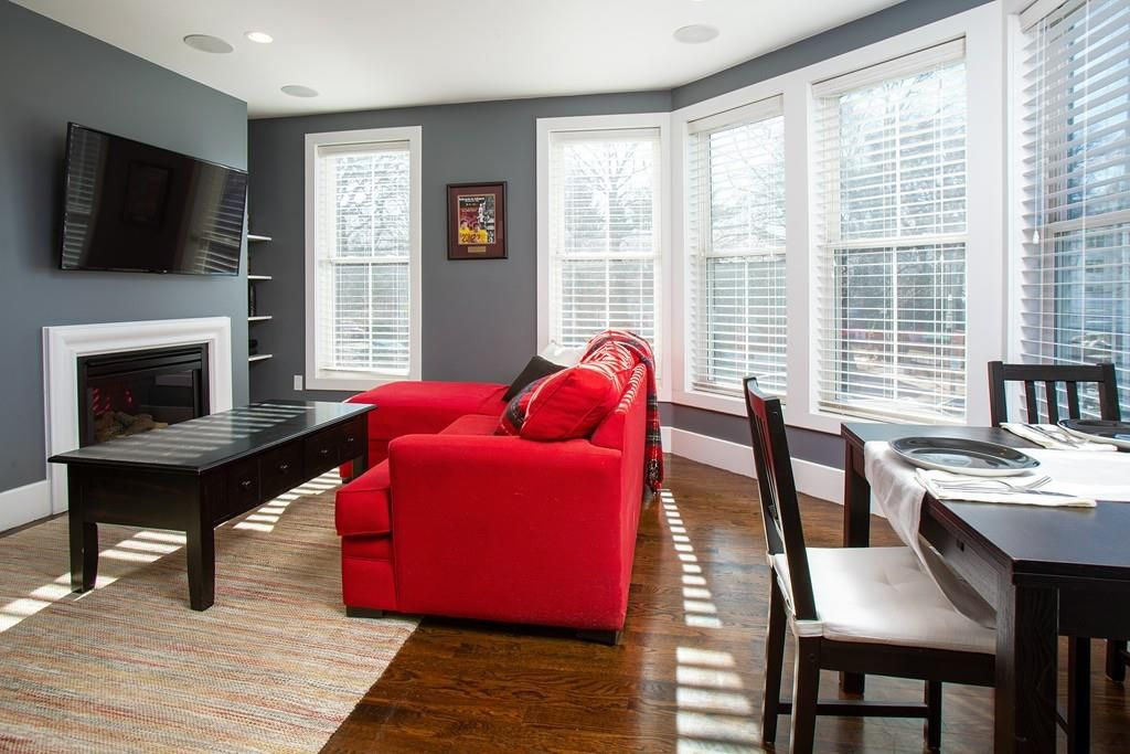 A living room with furniture, including a prominently placed couch, and there's a bay window.