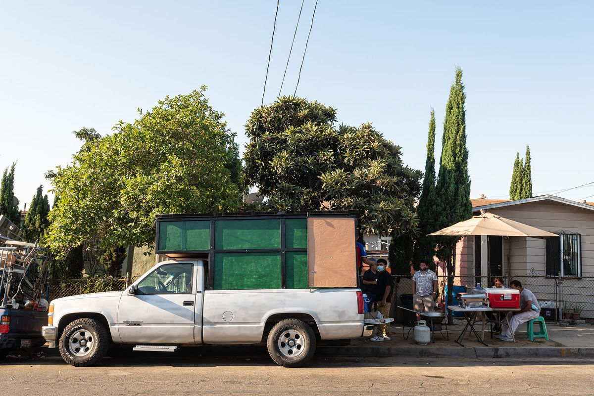 一辆带着封闭床的卡车停在餐桌旁的人行道上。