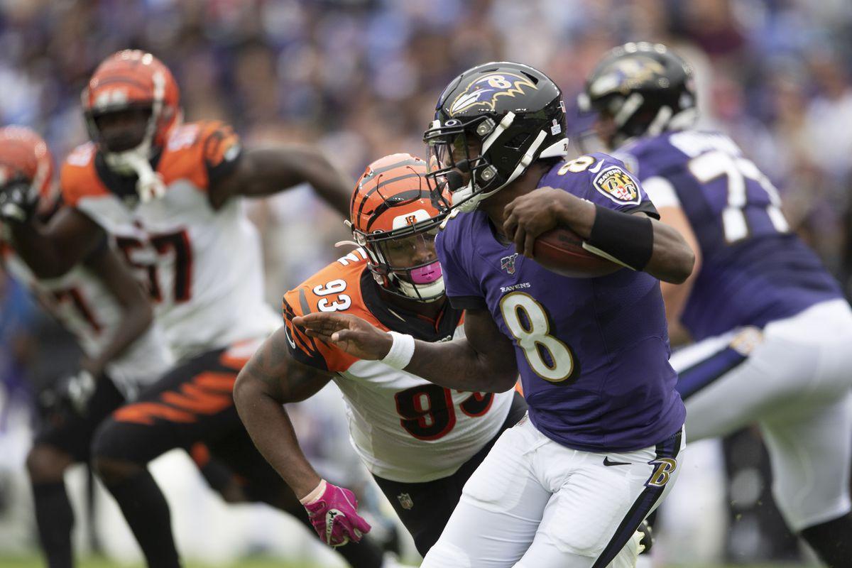 Baltimore Ravens quarterback Lamar Jackson runs as Cincinnati Bengals defensive tackle Andrew Brown defends during the first half at M&T Bank Stadium.