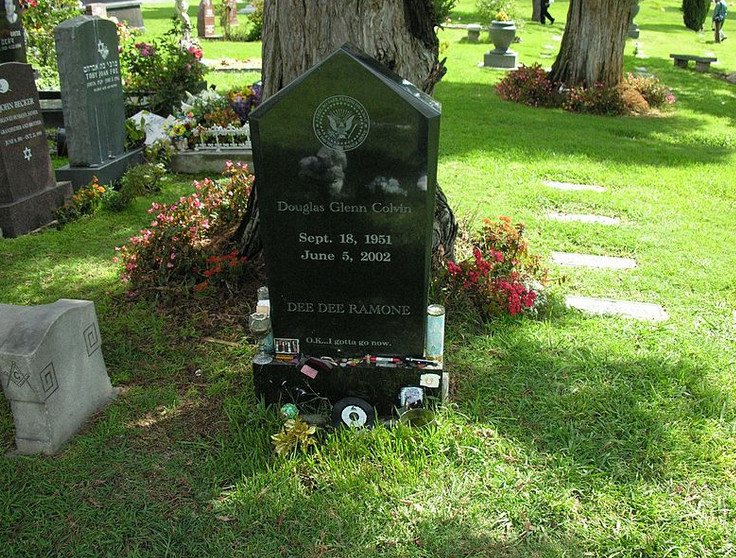 A black gravestone in front of a tree. The words on the gravestone read Douglas Glenn Colvin, Dee Dee Ramone, O.k...I gotta go now. There is grass and other gravestones surrounding this gravestone.
