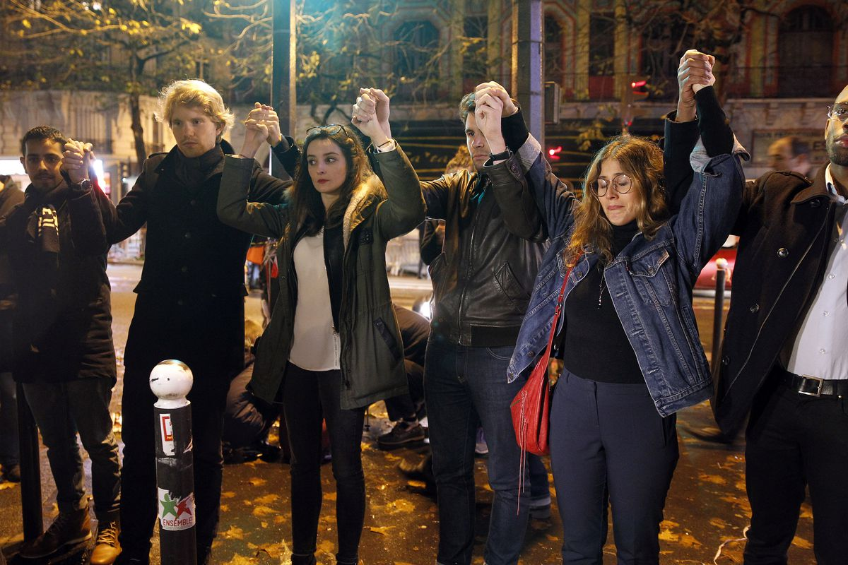 People gather at a memorial set up near the Bataclan theatre in Paris, to pay respects to the victims of a series of deadly attacks on November 20, 2015, in Paris, France.