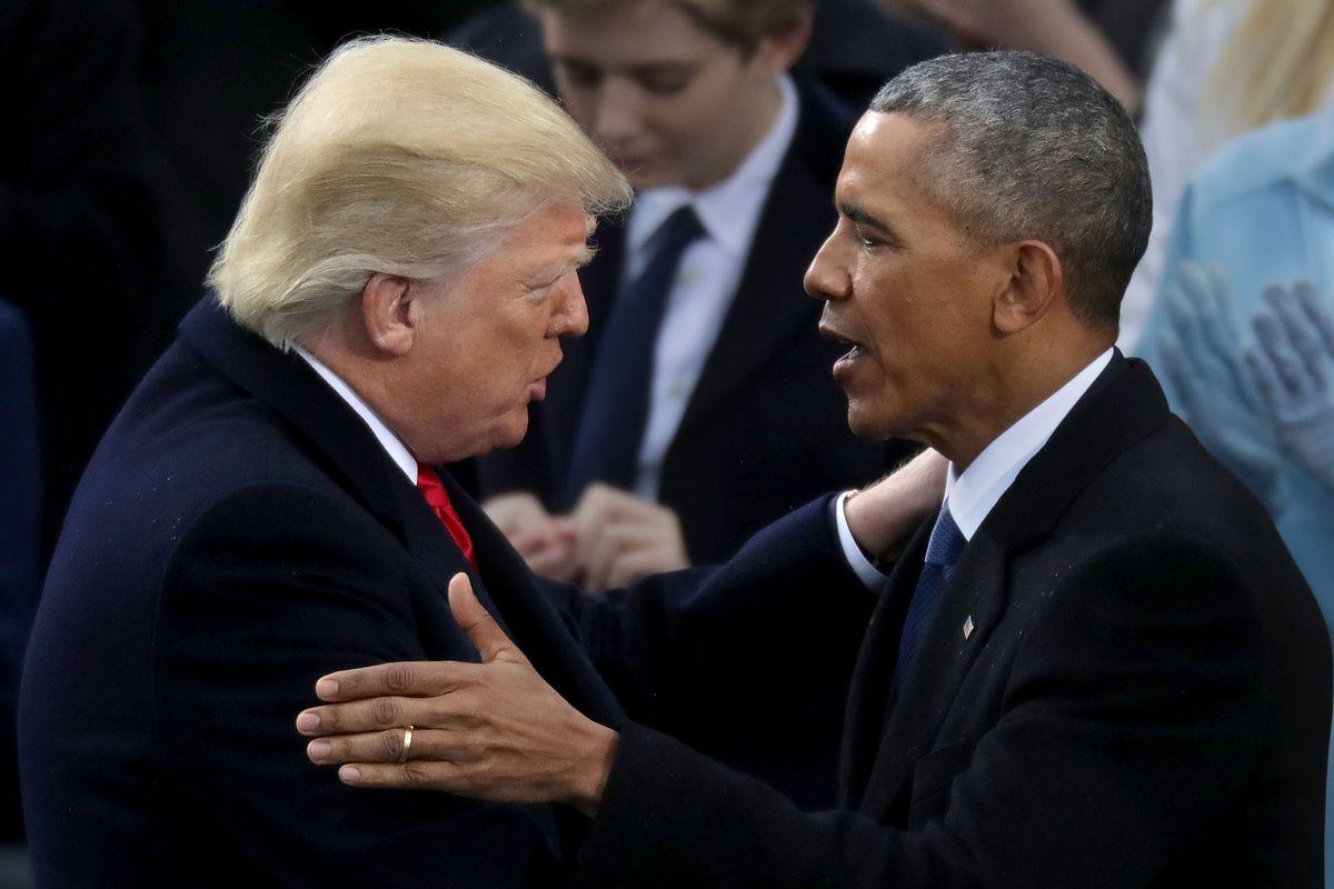 Barack Obama and Donald Trump shake hands.