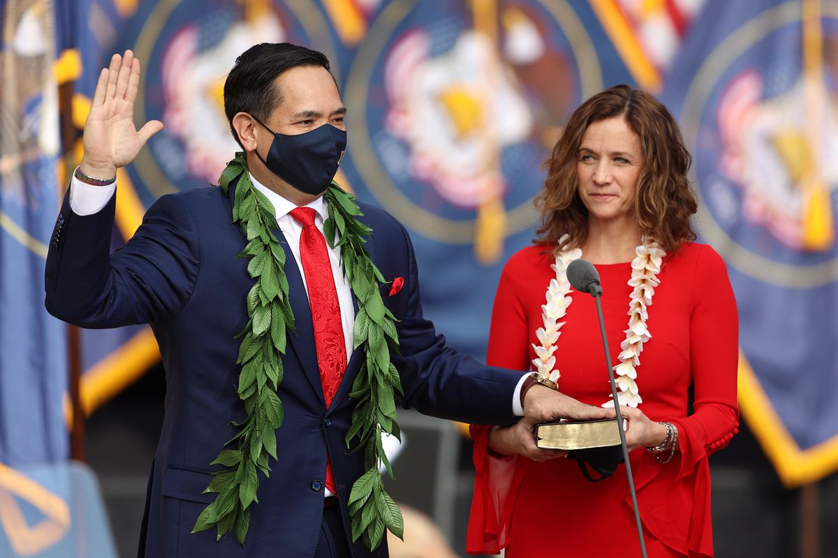Sean Reyes, Utah Attorney General, lays his hand on the Bible held by his wife, Saysha, to take his oath of office.