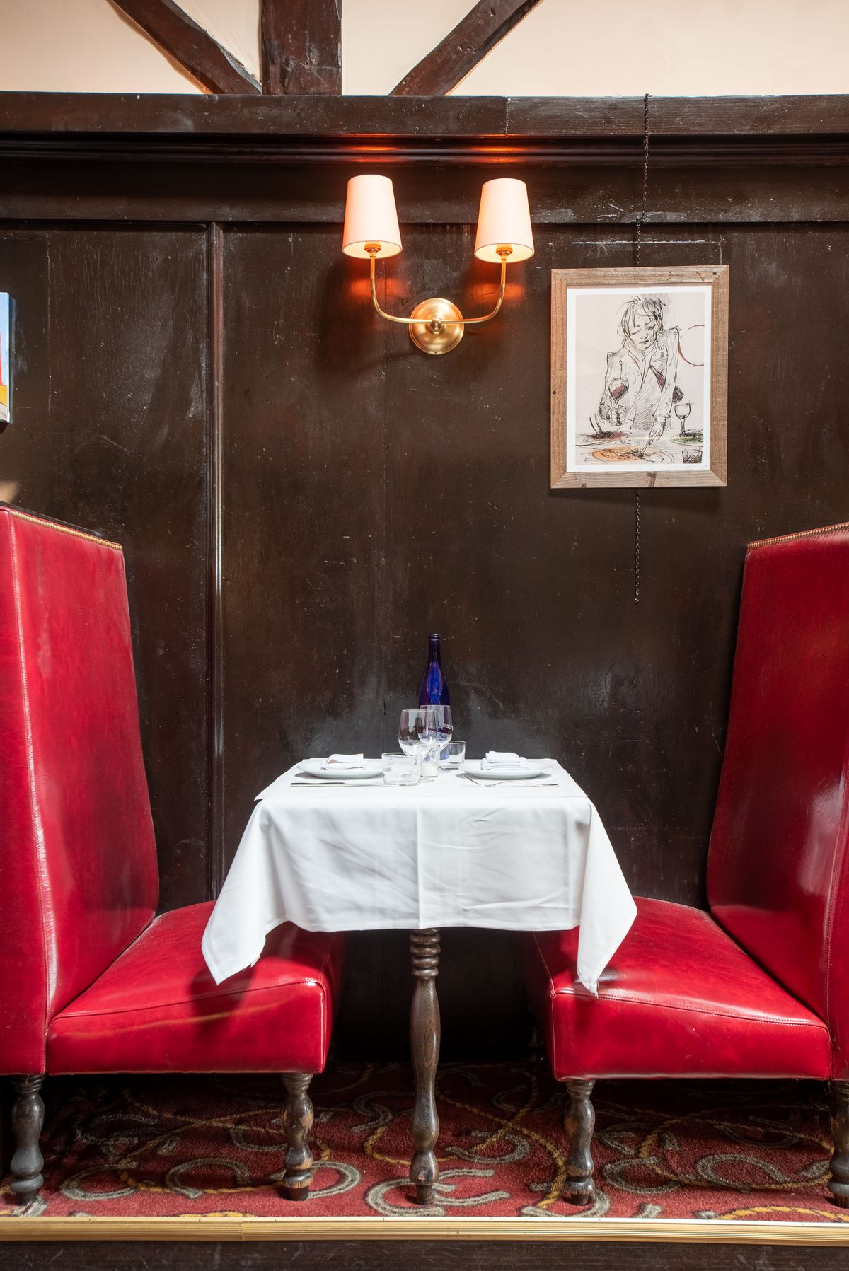 A close shot of tall booths and white tablecloths at an aging bar.