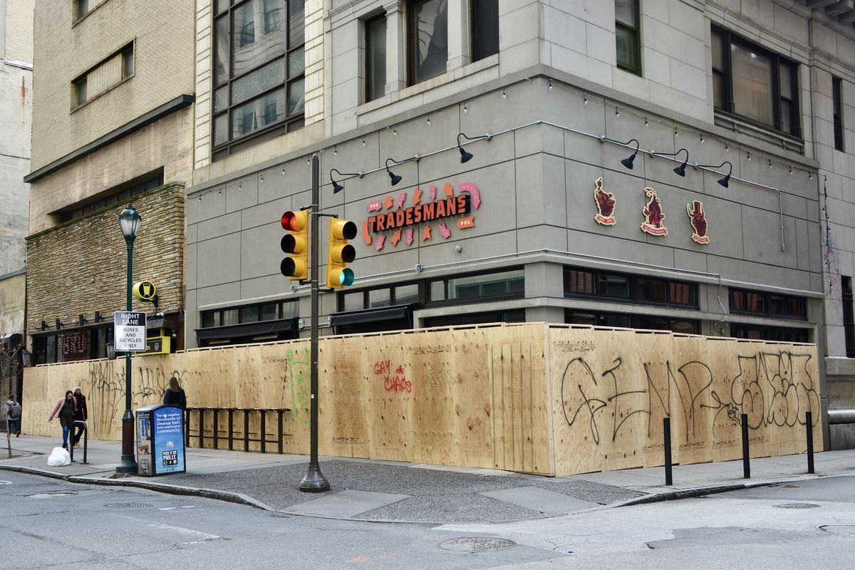 corner restaurant boarded up with sign that says tradesmans