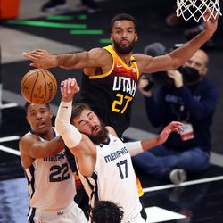 Utah Jazz center Rudy Gobert (27) hits the ball away from Memphis Grizzlies center Jonas Valanciunas (17) as the Utah Jazz and the Memphis Grizzlies play in game 5 at Vivint Arena in Salt Lake City on Wednesday, June 2, 2021.