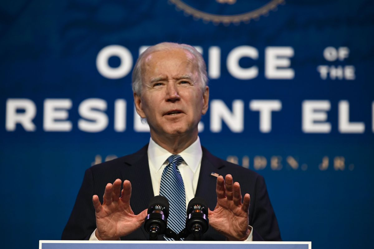 """Joe Biden speaking at a podium with """"Office of the president-elect"""" behind him."""