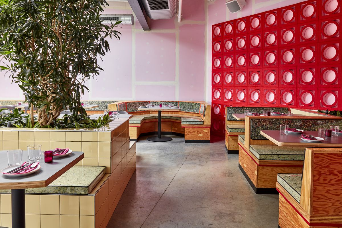 The inside of a restaurant with angular booths and a red and pink wall art installation.