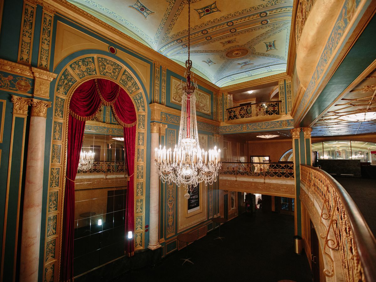 The interior of the Detroit Opera House. There is a chandelier hanging from the ceiling. The walls are painted with intricate colorful designs. There are balconies with seating.