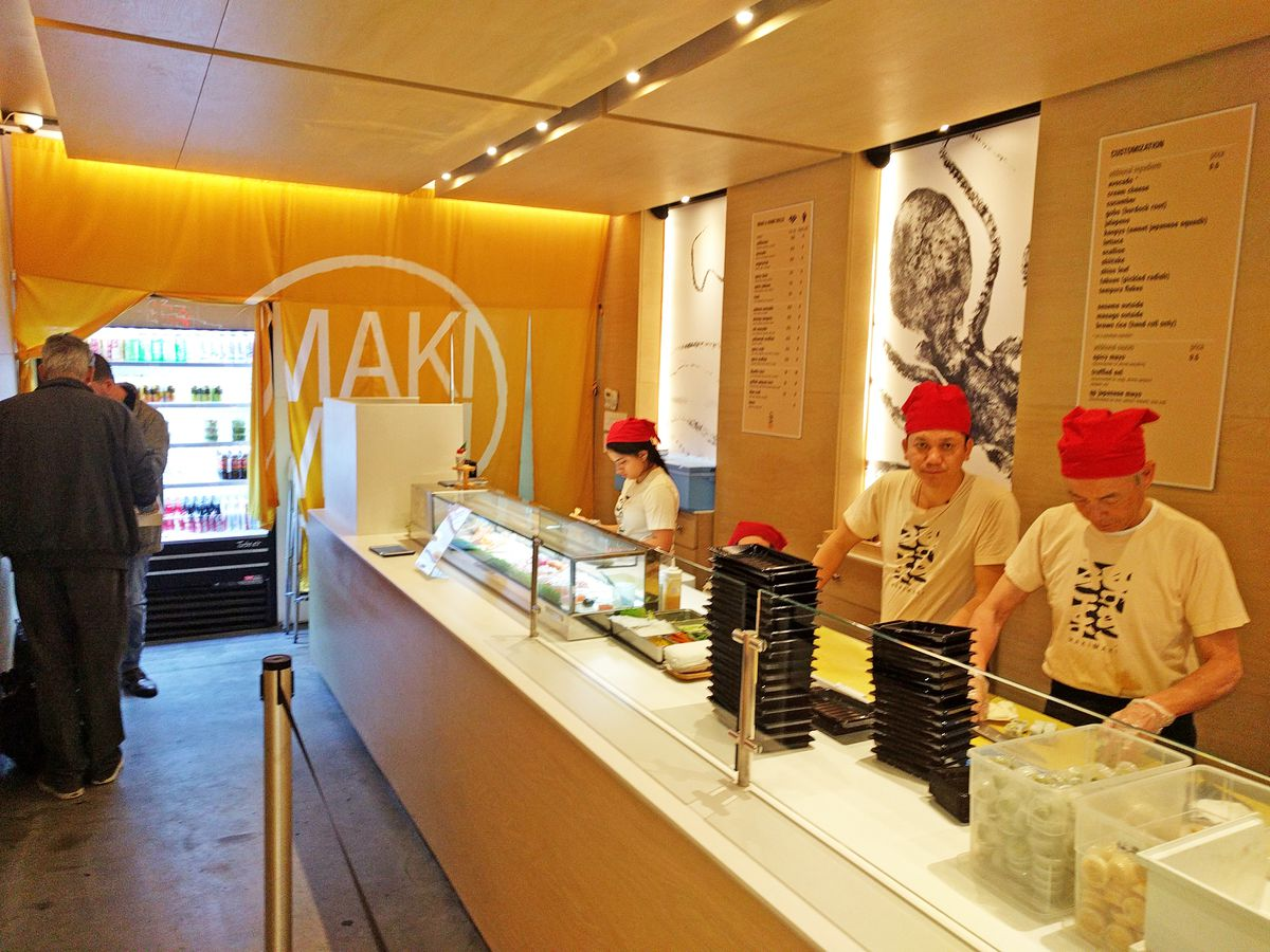 Three people dressed in uniform manning the sushi assembly line inside the restaurant.
