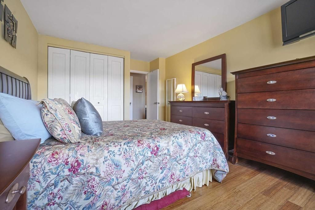 A bedroom with a bed and two dressers.