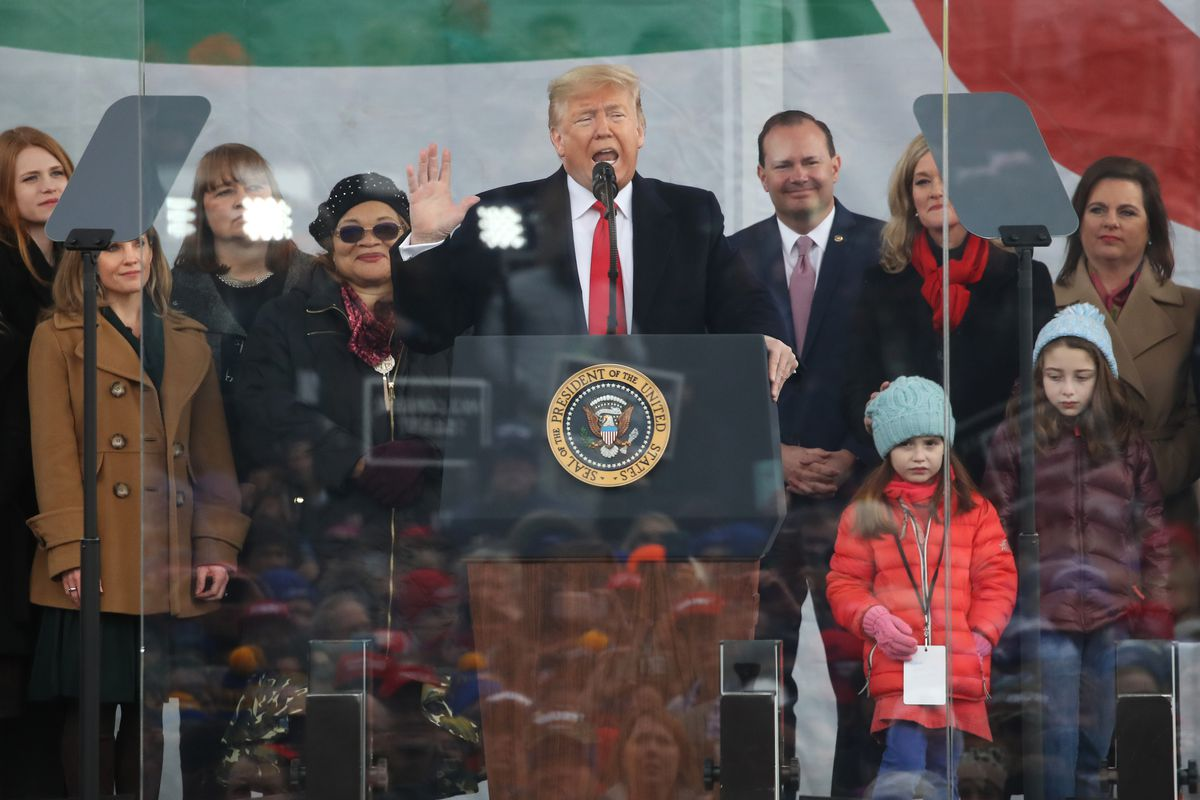 Donald Trump speaks at a podium, surrounded by attendees at the March for Life.