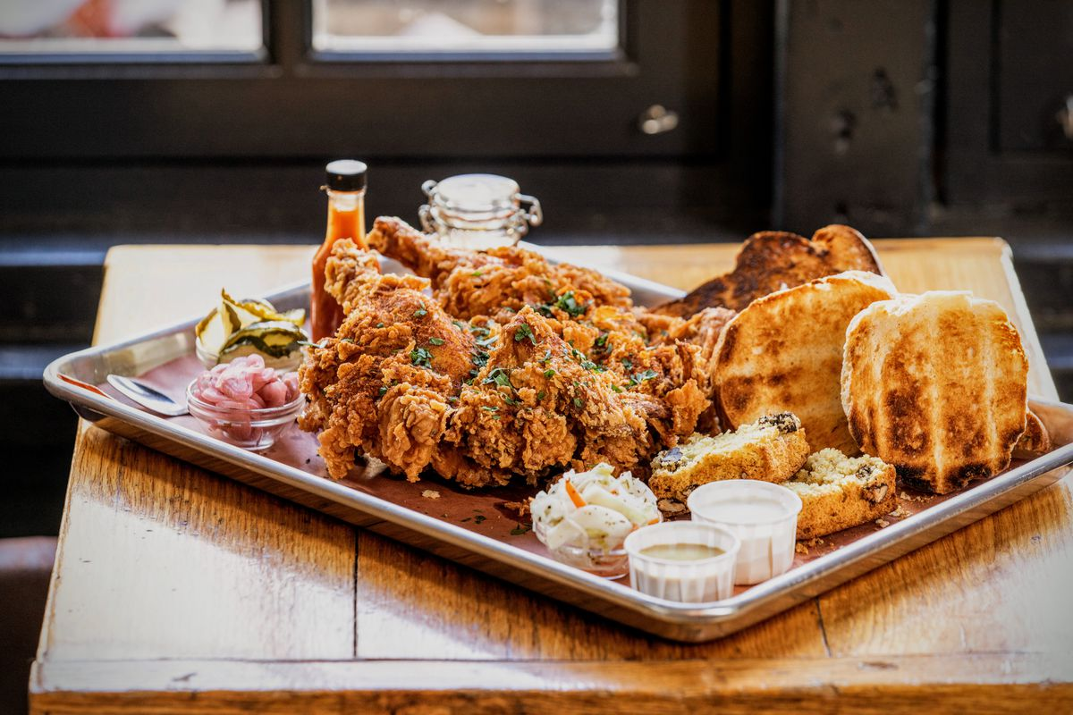 tray with fried chicken, bread, and condiments