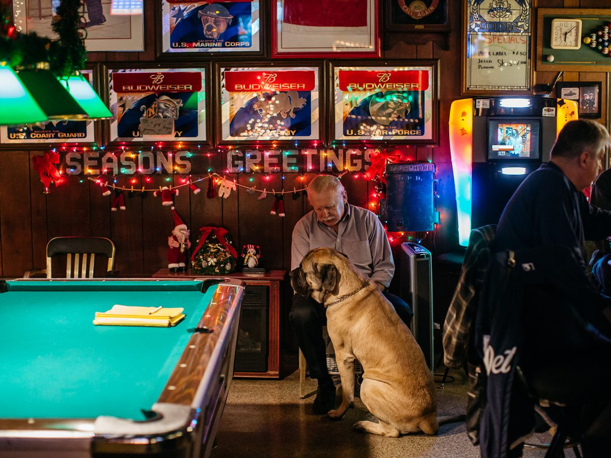 """A man sits inside the dark interior of Abick's with a large brown bar dog next to a billiard table. A sign reading """"Seasons Greetings"""" is lit up with Christmas lights behind him."""