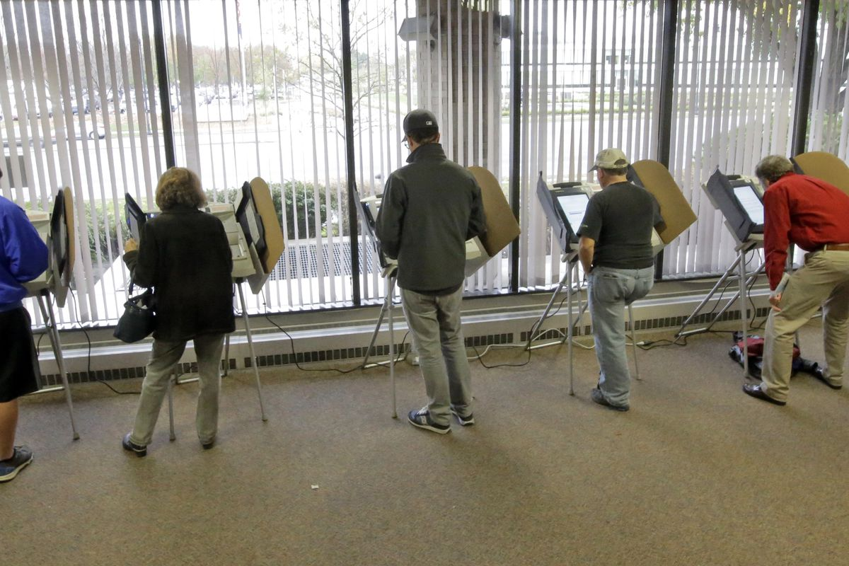 FILE - In this Nov. 1, 2016 file photo, people vote during early voting for the 2016 General Election at the Salt Lake County Government Center, in Salt Lake City. The state of Utah will use $4.1 million in federal grant money to help buy new voting equip