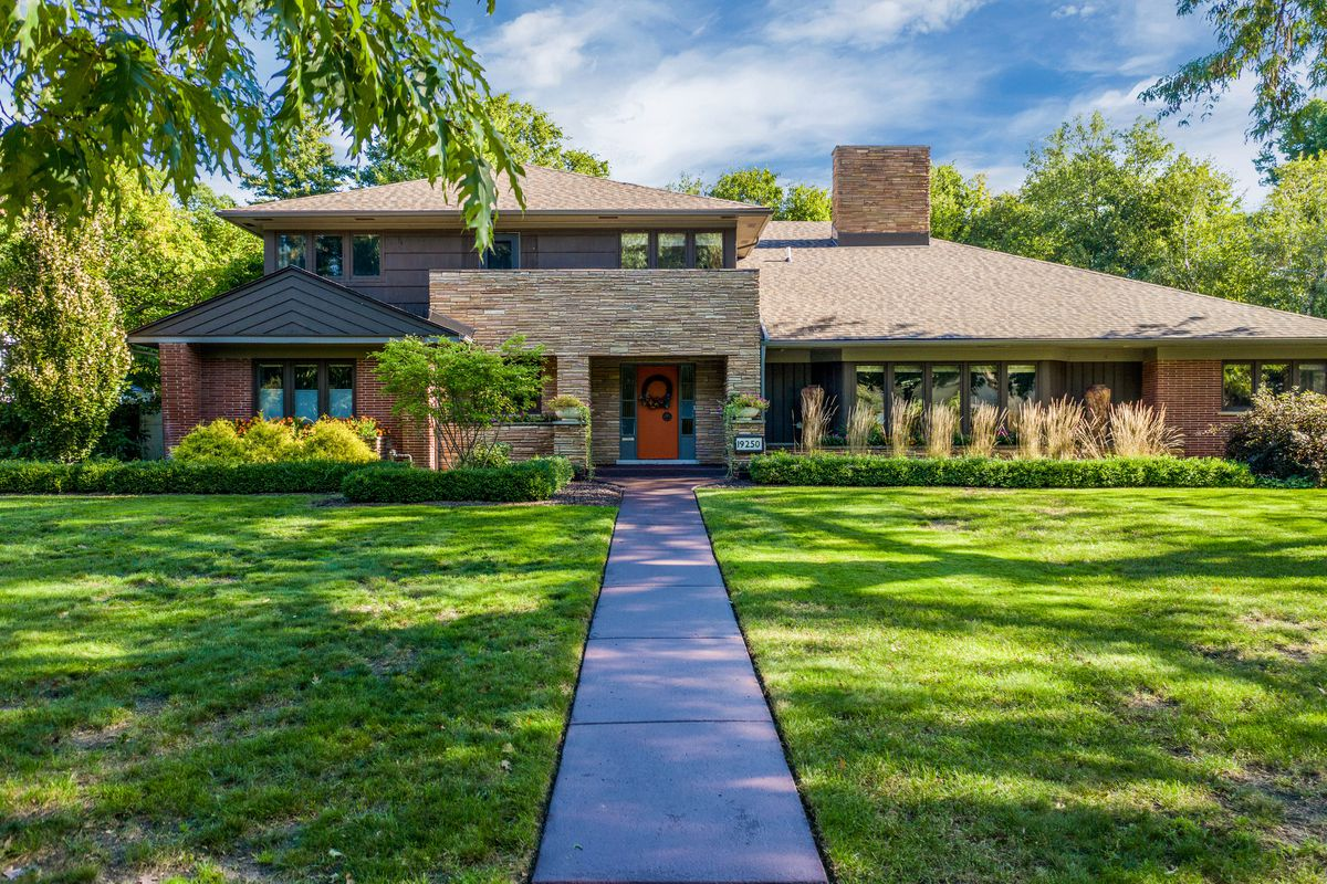 A large lawn and straight cement walkway leads to a long two-story home.