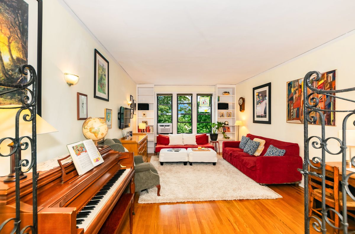 A living room with hardwood floors, three small windows, two red couches, a beige rug, and a piano.