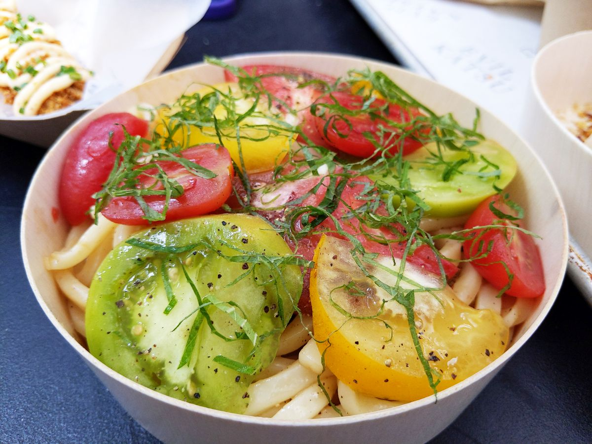 Yellow, red, and green tomato wedges in a bowl on top of thick white noodles.