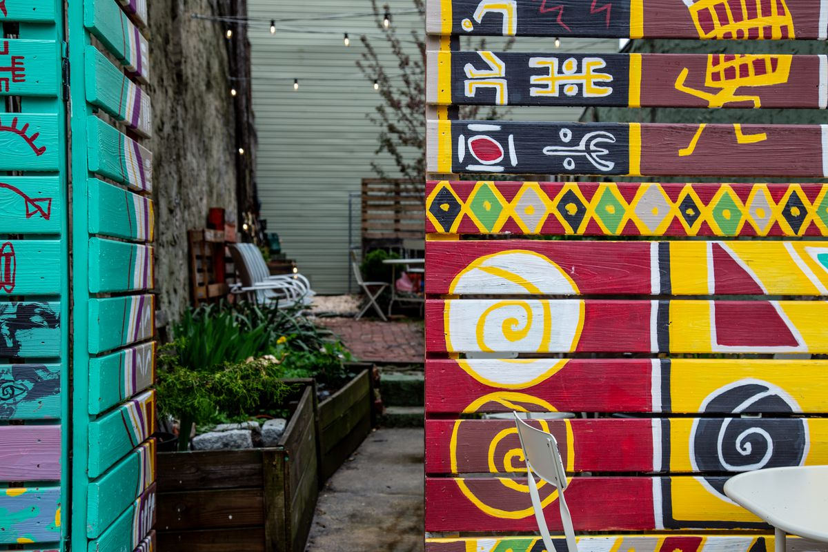 a colorfully painted wooden gate and wall with an outdoor patio area and chairs at franny lou's porch