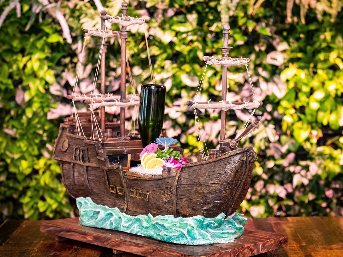 A giant pirate ship holds a shareable cocktail. It sits on a wooden table in front of a leaf-covered wall.