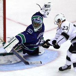 Los Angeles Kings right wing Dustin Brown (23) sends a shot past Vancouver Canucks goalie Roberto Luongo (1) during the second period of Game 2 of a first-round NHL hockey Stanley Cup playoff series in Vancouver, British Columbia, Friday, April, 13, 2012.