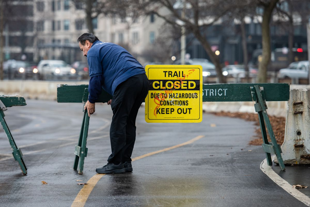 Dan Garcia with Chicago Parks District Security sets up a barricade to close down a section of the lake front running and biking trail near North Avenue due to hazardous conditions, Friday, Jan. 10, 2019, in Chicago.