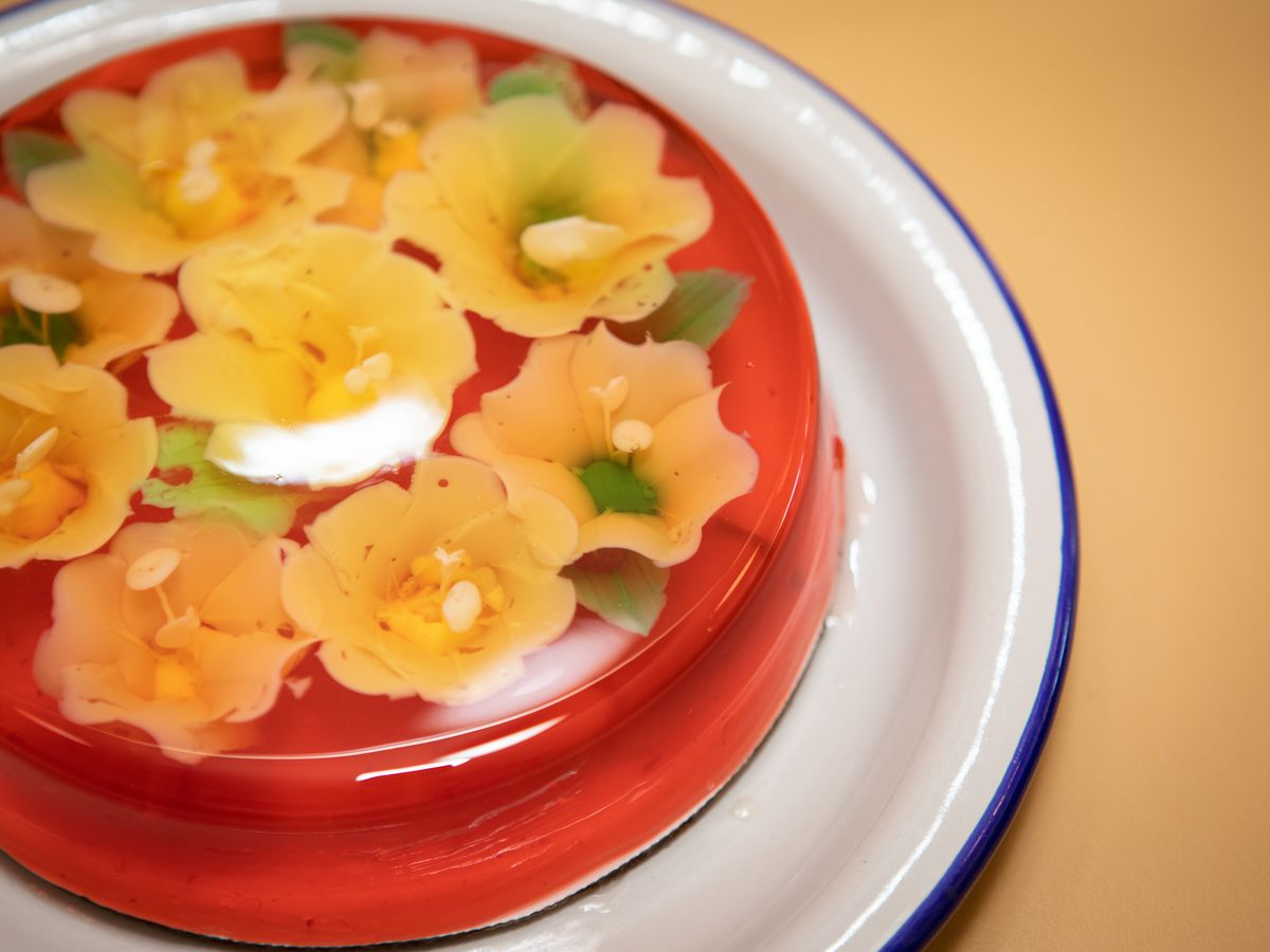 A close up photo of a red jelly cake infused with yellow flower shapes and green leaves that is resting on a white plate with a blue rim
