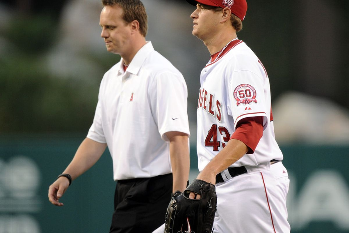 ANAHEIM, CA - AUGUST 15:  Garrett Richards #43 of the Los Angeles Angels leaves the game with a trainer after an injury during the first inning at Angel Stadium of Anaheim on August 15, 2011 in Anaheim, California.  (Photo by Harry How/Getty Images)