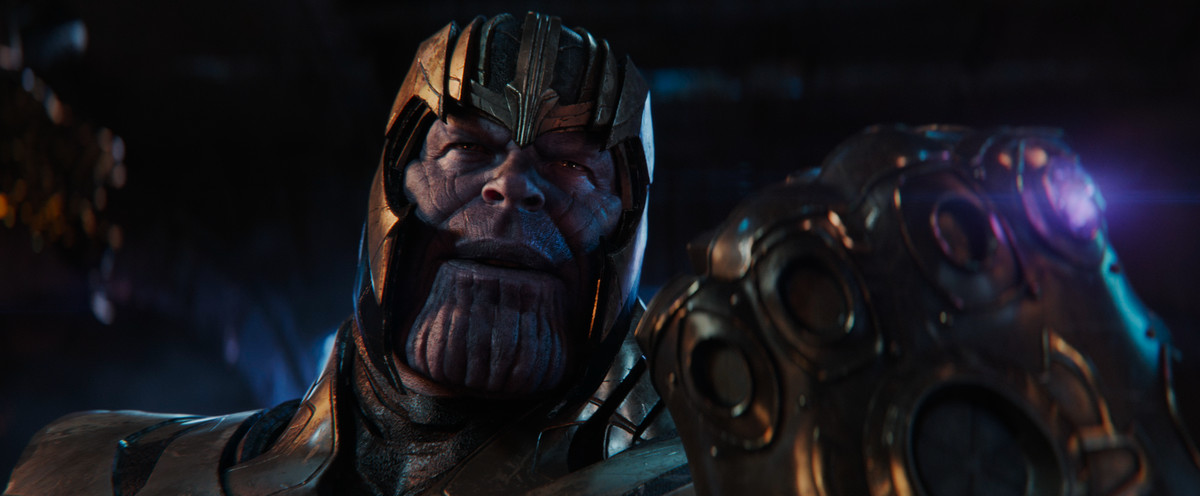 thanos holds up the infinity gauntlet and his one stone, the purple mind gem
