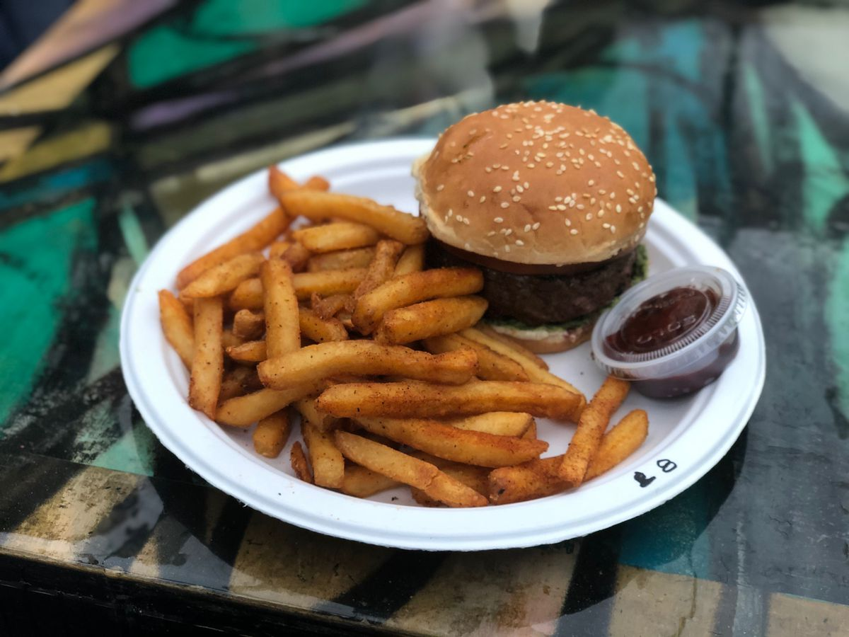 A white paper plate sitting on a table at Pakistani restaurant BK Jani featuring spicy fries, tamarind ketchup, and a burger