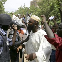 Sudanese protesters chant slogans as riot police stand guard in Khartoum, Sudan, Friday, Sept. 14, 2012, as part of widespread anger across the Muslim world about a film ridiculing Islam's Prophet Muhammad. Germany's Foreign Minister says the country's embassy in the Sudanese capital of Khartoum has been stormed by protesters and set partially on fire. Minister Guido Westerwelle told reporters that the demonstrators are apparently protesting against an anti-Islam film produced in the United States that denigrates the Prophet Muhammad.