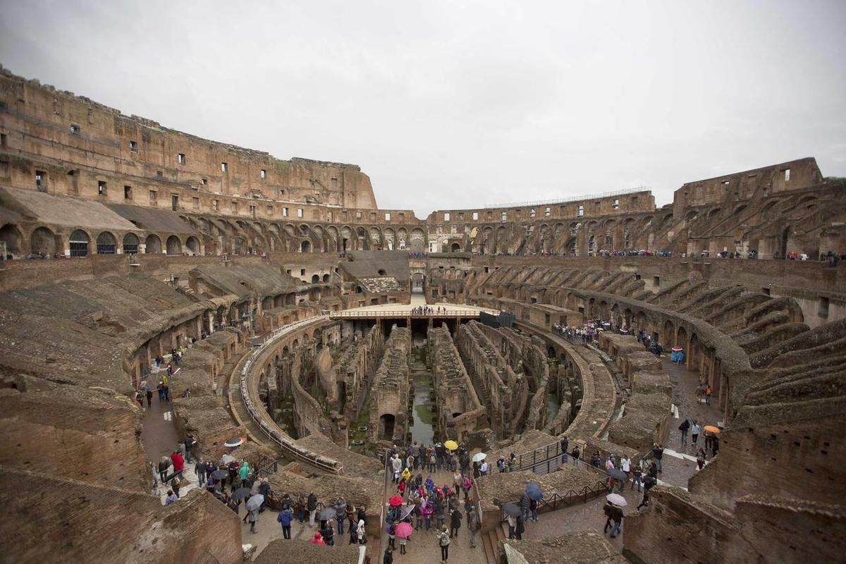 Tourists gather at Rome's Colosseum, Friday Nov. 7, 2014. An archaeologist's proposal to return the Colosseum's storied arena to its original state, when gladiators sparred with lion, has sparked a lively debate over appropriate uses of the monument that